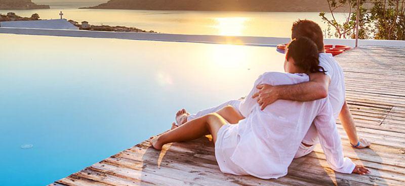 Zonvakantie, man en vrouw genieten van de zonsondergang